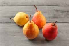在灰色木书桌上的四个成熟红色和黄色梨 库存图片