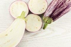 在灰色木头的新鲜的未加工的紫色镶边茄子 库存图片