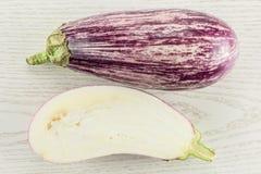 在灰色木头的新鲜的未加工的紫色镶边茄子 免版税库存图片
