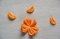在灰色木板的三个蜜桔橙色切片有赠送阅本空间的 新鲜的未加工的橘子和被剥皮的黄色蜜桔 库存图片