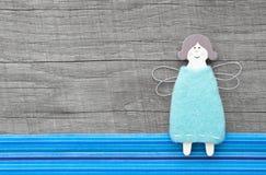 在灰色木背景的一点天使玩偶与蓝色条纹 免版税库存照片