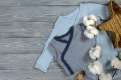 在灰色木背景的两蓝色婴儿紧身衣裤 购物ma 库存照片