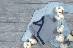 在灰色木背景的两蓝色婴儿紧身衣裤 购物ma 免版税库存图片