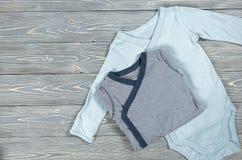 在灰色木背景的两蓝色婴儿紧身衣裤 购物ma 免版税图库摄影