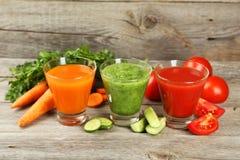 在灰色木背景的新鲜的蕃茄、红萝卜和黄瓜汁 免版税库存照片