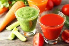 在灰色木背景的新鲜的tomate、红萝卜和黄瓜汁液 免版税库存照片
