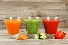 在灰色木背景的新鲜的tomate、红萝卜和黄瓜汁液 免版税库存图片