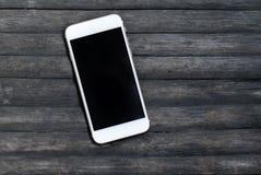 在灰色木背景的白色智能手机 个人设备大模型 免版税库存图片