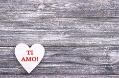 在灰色木背景的装饰白色木心脏与在上写字我爱你用意大利语 库存照片