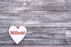 在灰色木背景的装饰白色木心脏充满在波兰语的字法爱 库存照片