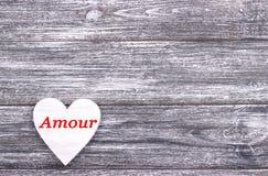 在灰色木背景的装饰白色木心脏充满字法爱用法语 免版税库存照片