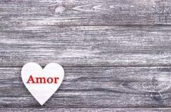 在灰色木背景的装饰白色木心脏充满字法爱用葡萄牙语 库存图片