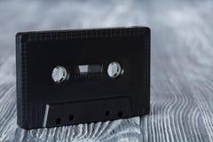 在灰色木背景的黑卡型盒式录音机 免版税库存照片
