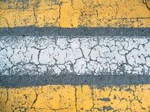 在灰色柏油路纹理、顶视图当难看的东西背景或墙纸的破裂的黄色和白色漆线 免版税库存图片