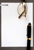 在灰色框架的白皮书与笔和太阳镜 免版税库存图片