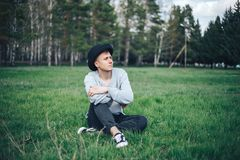 在灰色毛线衣休息的年轻人模型坐在帽子的草 免版税库存图片