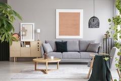 在灰色沙发上的桃红色海报在与木桌的客厅内部在碗柜附近 实际照片 免版税图库摄影