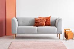 在灰色沙发的橙色枕头在灰色客厅内部 实际照片 库存照片
