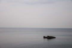 在灰色海中间的孤立岩石 免版税库存图片