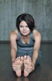 在灰色混凝土墙背景的少妇实践的瑜伽  库存照片