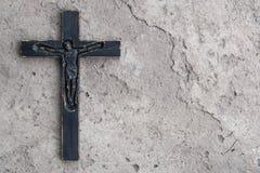 在灰色混凝土的黑木耶稣受难象有镇压背景 库存图片