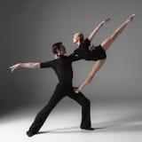 在灰色演播室的两个年轻现代跳芭蕾舞者 免版税库存照片
