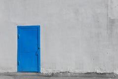 在灰色灰泥大厦墙壁上的蓝色金属门 免版税库存图片