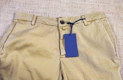 在灰色牛仔布裤子-新的衣裳的空白的标签 免版税库存图片