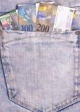 在灰色牛仔裤口袋的瑞士法郎笔记 库存照片