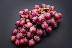在灰色的红色成熟葡萄 库存照片