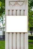 在灰色石柱子的空白的广告牌在城市环境里 免版税库存照片