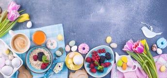 在灰色石背景的可口春天早餐 桃红色和薄荷的颜色新鲜的郁金香花束  色的小和大 免版税库存图片