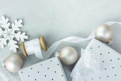在灰色石背景的圣诞节新年构成礼物盒白色丝绸卷曲的丝带雪剥落装饰品球 免版税库存照片