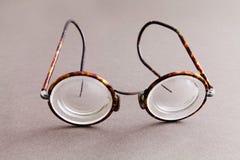在灰色纸背景的老时尚设计眼镜镜片 葡萄酒样式人时装配件 宏观看法 库存照片