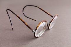 在灰色纸背景的老时尚设计眼镜镜片 葡萄酒样式人时装配件 宏观看法 免版税库存图片