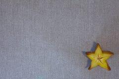 在灰色纺织品的阳桃切片 免版税库存照片