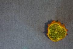 在灰色纺织品的Kiwano切片 库存照片