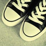 在灰色纺织品背景的黑帆布运动鞋 免版税库存图片