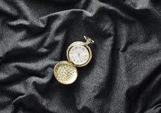 在灰色织品背景的古色古香的金黄怀表 免版税库存图片