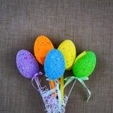 在灰色织品背景的多彩多姿的复活节彩蛋  复活节快乐的题字 复制空间 库存图片