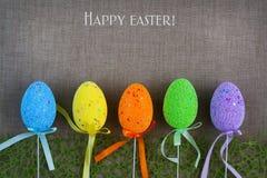 在灰色织品背景的多彩多姿的复活节彩蛋  复活节快乐的题字 复制空间 免版税库存图片