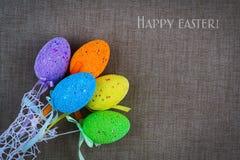 在灰色织品背景的多彩多姿的复活节彩蛋  复活节快乐的题字 复制空间 库存照片
