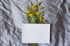 在灰色织品背景的白色板料与黄色花 免版税库存图片