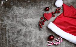 在灰色织地不很细木背景的红色圣诞老人帽子 库存图片