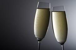 在灰色背景之前的二块香槟玻璃 库存图片