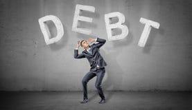 在灰色背景的一个商人蜷缩在做在他上的大具体信件下一个词债务 库存照片