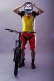 头戴在灰色背景的专业骑自行车者一件盔甲 库存照片