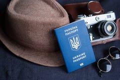 在灰色背景的乌克兰旅行护照 太阳镜,帽子 在背景的葡萄酒照相机 欧盟签证自由存取 浅dept 免版税库存图片
