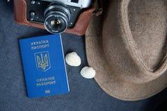 在灰色背景的乌克兰旅行护照 太阳镜,帽子 在背景的葡萄酒照相机 欧盟签证自由存取 浅dept 免版税库存照片