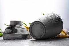 在灰色背景的发光的金属鸡尾酒搅拌器 在一张灰色桌上的被打开的灰色容器 做的鸡尾酒一个瓶子 免版税库存图片